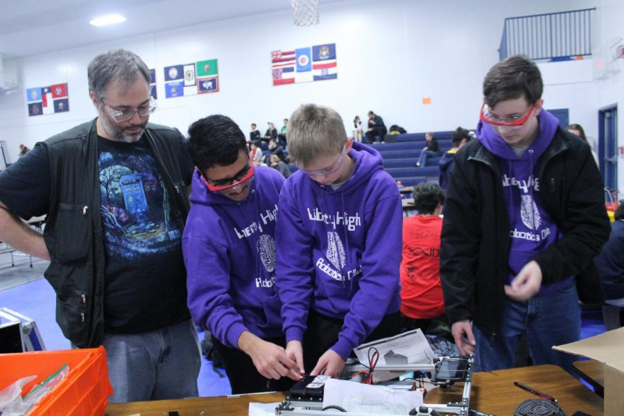 Abhishek Aryal, Kyle Dominy, and Andrew Burkhart working with an advisor at a competiton.