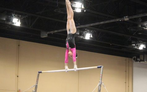Addison Fishman, freshman, performing on bars during her gymnastics competition