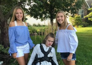 Gabbie, Maddie, and Carlie Schroeder pose in the outdoors, all wearing blue and white.