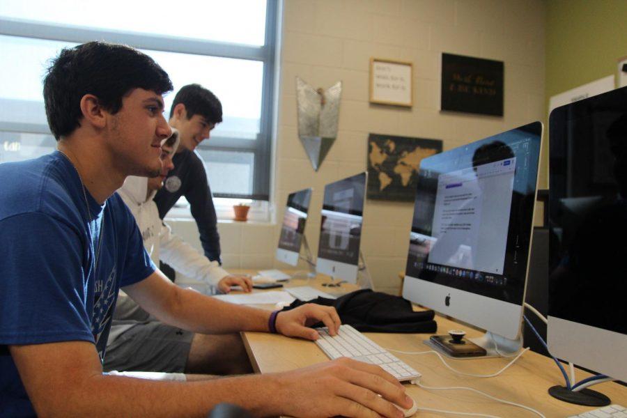 Zack Anderson, Max Tafolla and Brody Fishman working in newspaper.