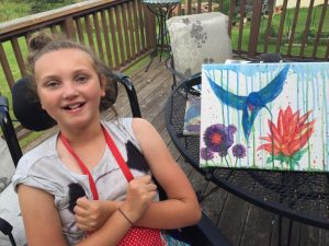 Anna with a painting she made of a hummingbird and flower.