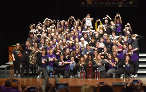Members of show choir pose with their trophies after storming the awards stage at North Polk High School.