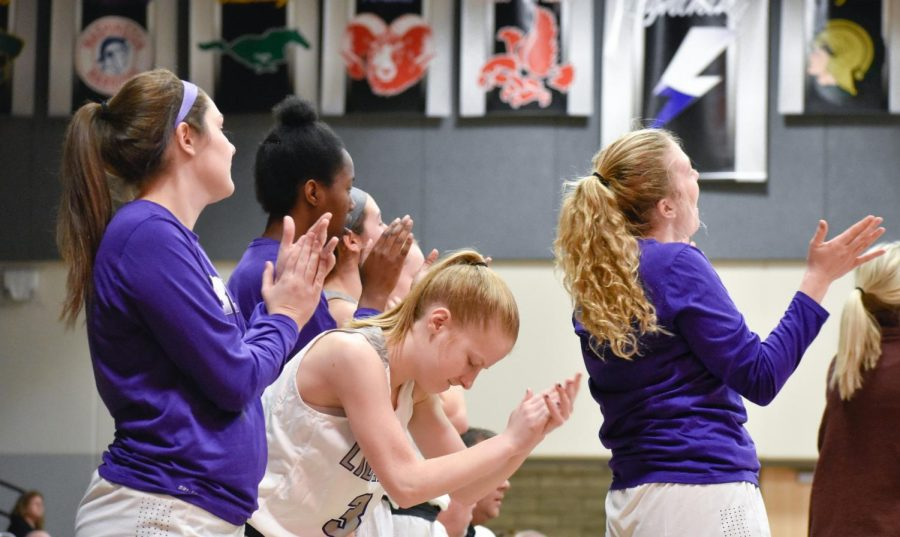 The girls hop off the bench and celebrate after a made basket.