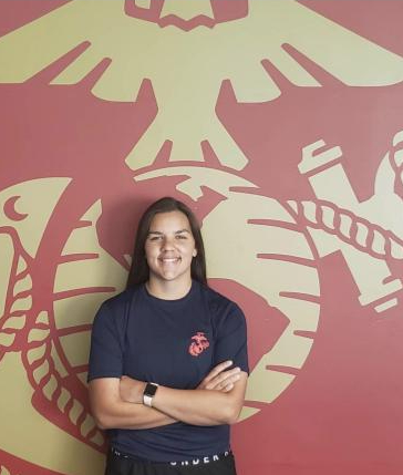 Miranda Jones, senior, poses in front of the Marines logo. She plans  to finish school early and leave Feb. 16.