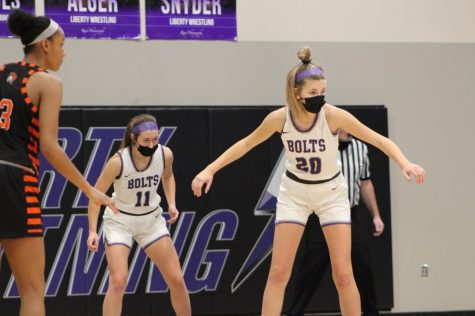 Ava Meyer and Kennedy Daugherty play defense in a home game at Liberty,
