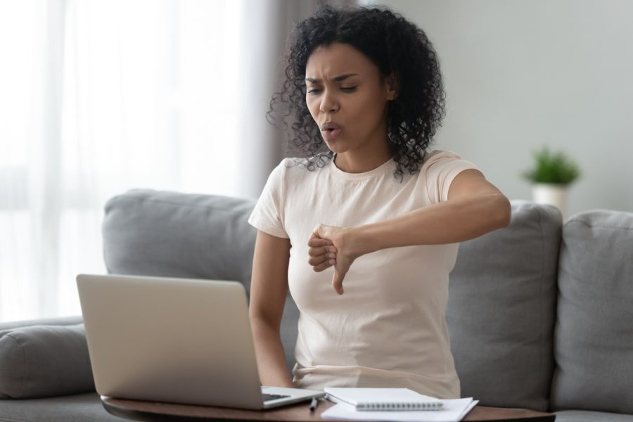 Woman looking at computer screen. She has a dislike for online school.