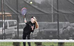 Ella Gilbert, freshman, reaches her racket to hit the tennis ball.