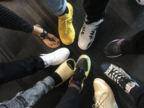 English Language Learners (ELL) students at Liberty show off their shoes, along with their teachers.